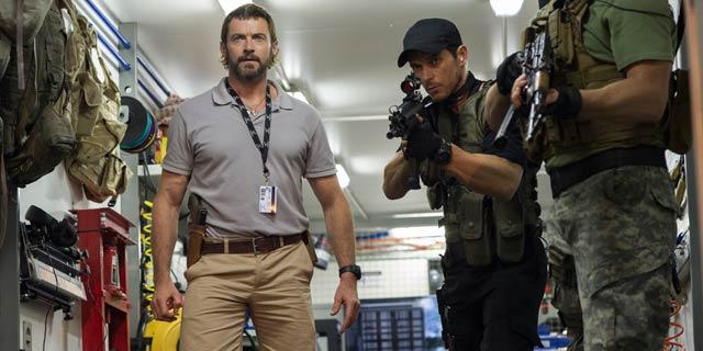Hugh Jackman é Vincent Moore em Chappie, o vilão que tenta destruir o amigável robô.
